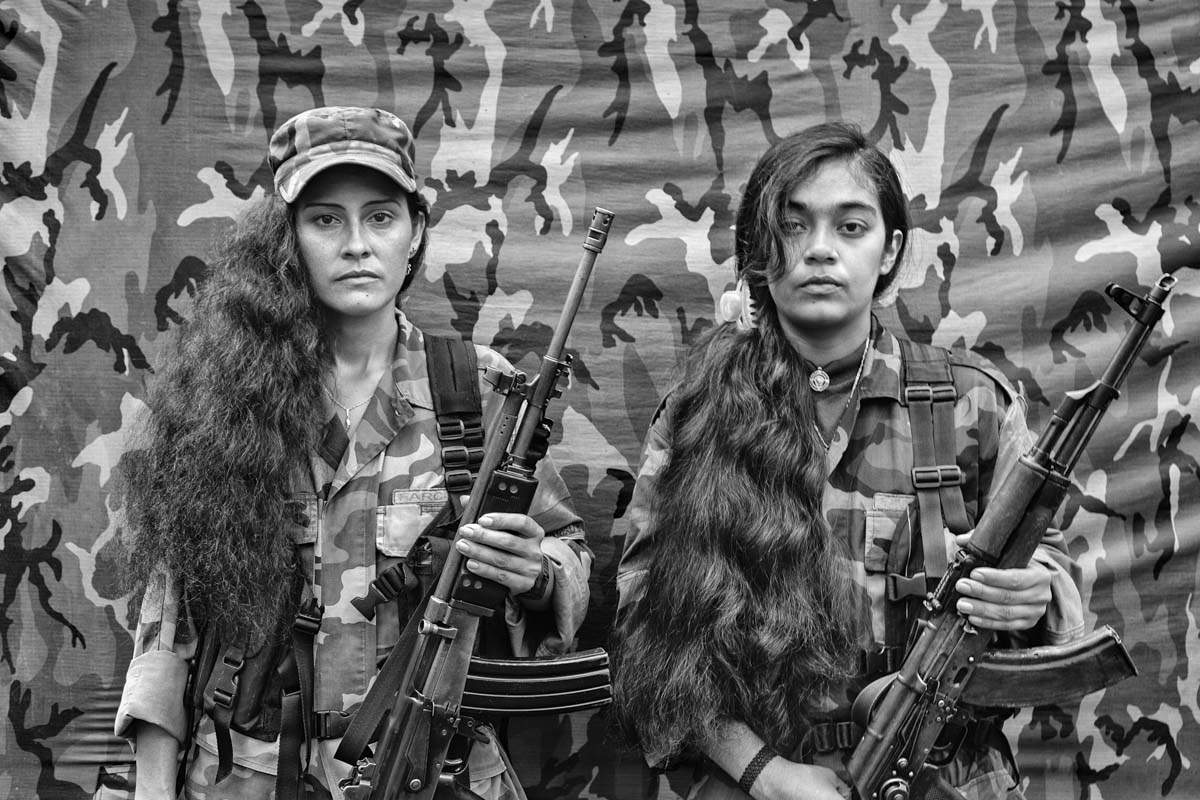 """SAN JUAN, CHOCÓ, COLOMBIA - NOVEMBER 2007. Judith and Isa (their war-based pseudonyms), two members of the Revolutionary Armed Forces of Colombia the Bloque Móvil Arturo Ruíz. The FARC-EP, a self-declared Marxist-Leninist guerrilla group in Colombia, has operated since 1964. The Bloque Móvil Arturo Ruíz is a special unit of the FARC-EP that fights in many different regions of Colombia. This unit acts as a """"quick reaction force"""" to help other sub-groups of FARC-EP. Women, like Judith and Isa, play a large role in the FARC-EP, with equal status and duties as their male counterparts."""