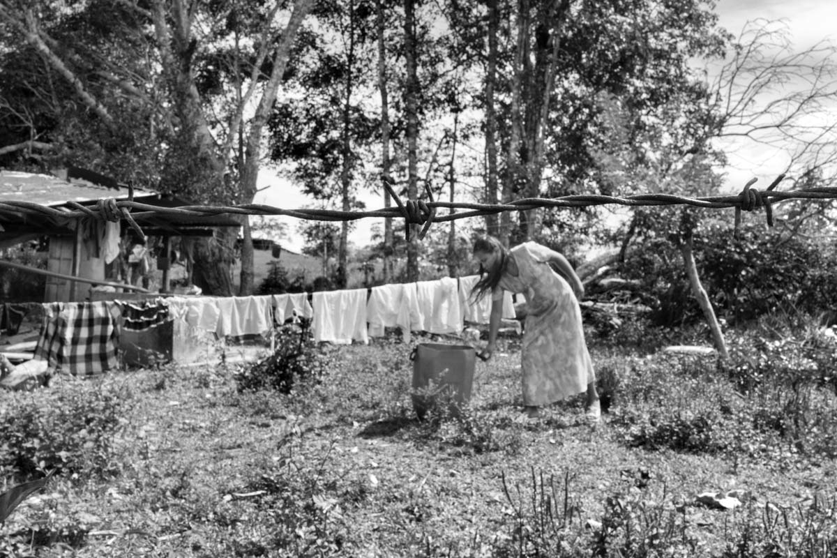 """SANTO DOMINGO, CAQUETÁ, COLOMBIA (2013) A woman, whose family members support the FARC-EP, hangs laundry in her garden. The Frente 14, the Frente 15, and the Domingo Biojó—units within the FARC-EP Southern Bloc—control this area of the Caguán River. This region has lived in a """"parallel state"""" to the rest of Colombia during the decades of conflict. Society here has experienced war as a """"living memory"""" and many have never known state authority except in its military capacity. The military in this region has been accused of committing numerous human rights violations. In reaction, swaths of Colombian society, here and elsewhere, have positioned themselves closer to the policy options of the FARC-EP guerrillas. Many see the possibility of a final peace deal as a chance to exchange weapons for political voice."""