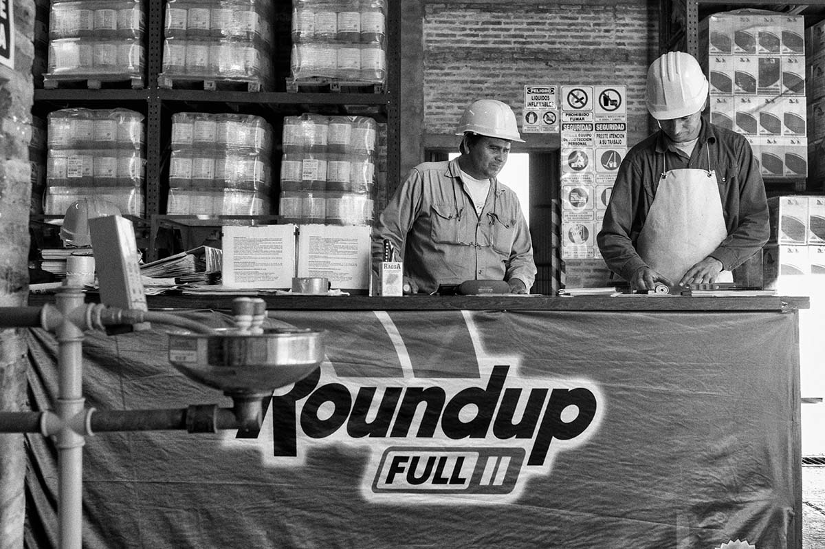 CHARATA, CHACO, ARGENTINA - MAY 2014: One group of workers in a store Monsanto in Charata review orders. behind them, hundreds of drums of Roundup - glyphosate - Monsanto's most controversial product. The consequences to the health of the local population - who lives with the spraying of agrochemicals such as glyphosate or some substances banned in European countries but permitted in-producing countries is systematically reported from Argentina and Brazil. Official studies show that in areas fumigated there is a rise in cases of cancer and malformations in newborns.