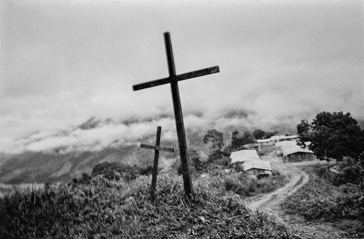 NARIÑO, COLOMBIA (2009) Two crosses along the road between the communities of El Naranjo and Remolino de Abajo, near the Patía River. In early 2009, this area was under the control of different right-wing paramilitary groups—the Rastrojos and the Black Eagles. With the unofficial backing of the army, the Black Eagles eventually ousted the Rastrojos. Today, this region is controlled by the FARC-EP. The area is strategically important for transport and movement, often of weapons and cocaine, as it is houses the route leading through the mountains to the Pacific coast. Access to this route is closed off to the outside world.