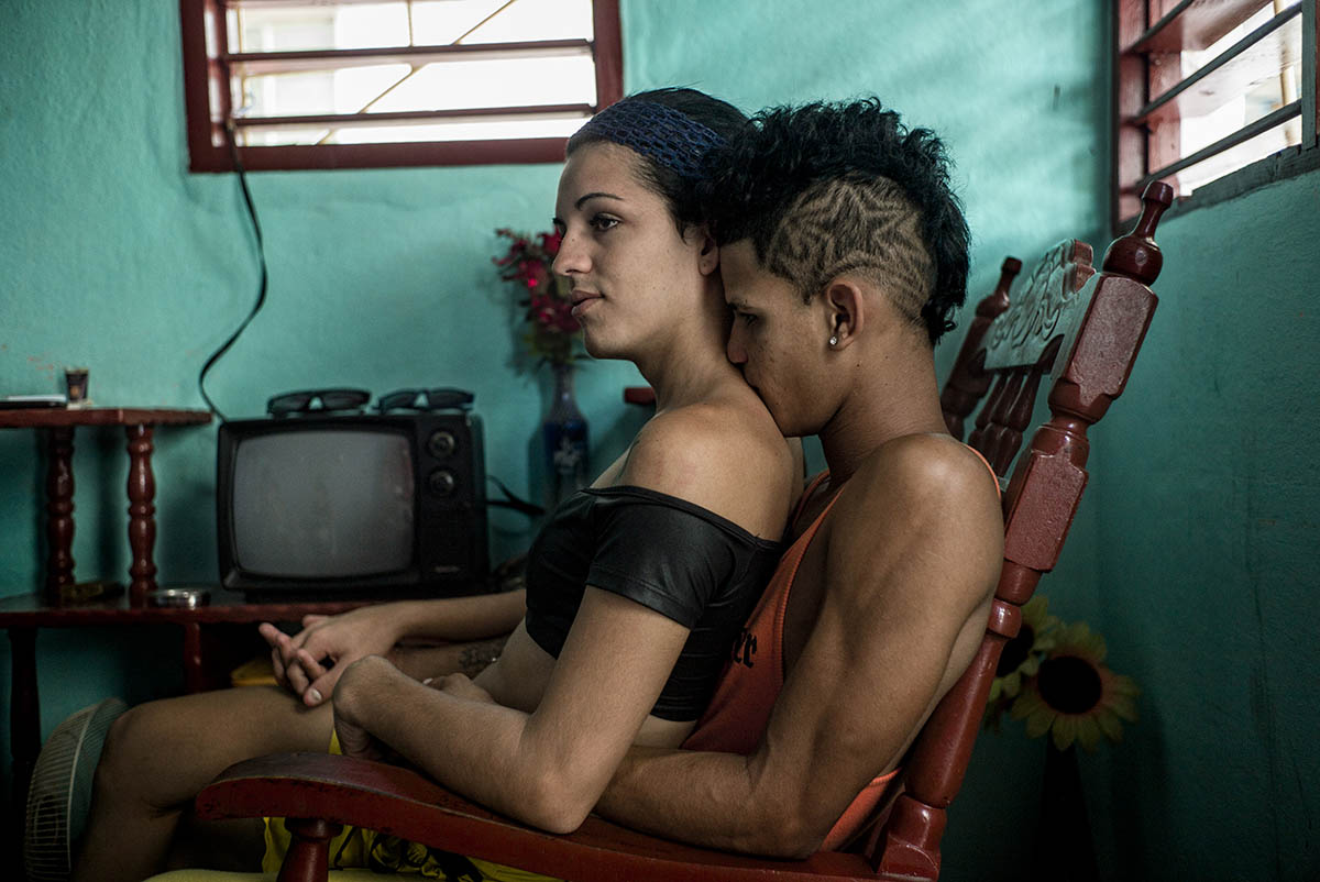 CUBA - MAY 2013: Deinna (left) and Gendris (DCH) are a couple. They are of Manzanillo, Granma province. She is trans and he is gay. Both come to Habana looking for opportunities. They live in Center Habana in a house of 20 square meters of one room rented with six other trans people. Both live off prostitution in Habana. They charge 5 CUC (3 euros) per customer. At home in Manzanillo, Gendrís is unemployed and Deinna works in the municipal museum. In Cuba, homophobia of State characterized the first four decades of the Revolution. Labor camps for homosexuals known as UMAP (Military Units to Aid Production), persecutions and discriminating measures marked the lives of thousands of Cubans. At present, this situation is part of the political reforms in a process of internal debate led from a state agency, by Mariela Castro, daughter of the current president. Pending legislation, the lesbian, gay, transgender and intersex fight for their rights.