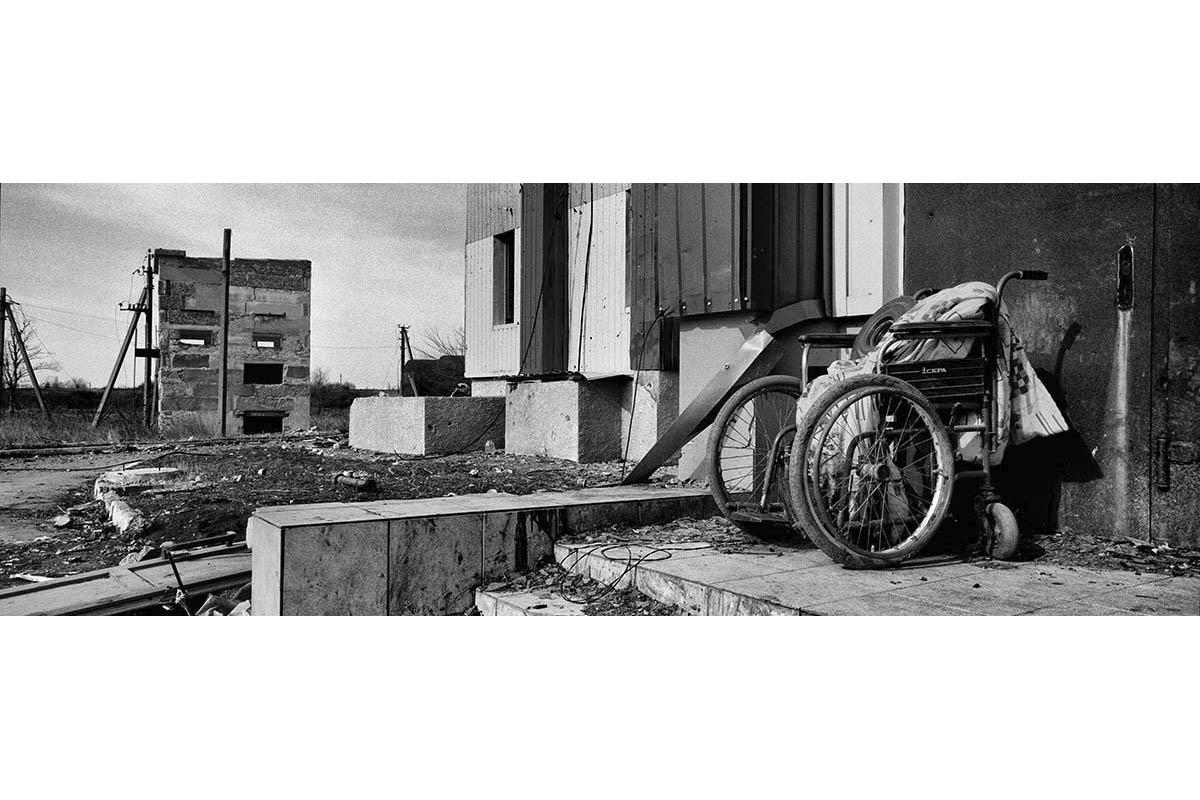 DONESTK, UKRAINE - FEBRUARY 2015: The remains of wheelchair ouside the destroyed cultural house of the community of Nikishino in Eastern Ukraine.Nikisino has been one of the major front lines in the war in the East of Ukraine. After the fall of the strategic town of Debaltseve in separatist hands, Ukrainian troops also left this strategic line of the front leaving the community fully mined and converted into ashes. The remains of the Nikishino community attest to the drastic consequences of the war on the civilian population in the East of Ukraine.
