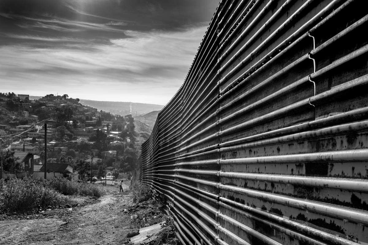 TIJUANA, BAJA CALIFORNIA, MEXICO - MARCH, 2017: A resident of Tijuana walks watching the wall that marks the border between Mexico and the US photographed from the Mexican side in the city of Tijuana. .