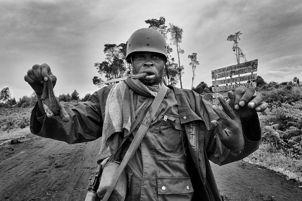 DEMOCRATIC REPUBLIC OF CONGO, NOVEMBER 2008: An FRDC (Congolese Army) soldier holds the sexual organs and hand of a dead CNDP (National Congress for People's Defense) soldier that he has amputated with a knife.