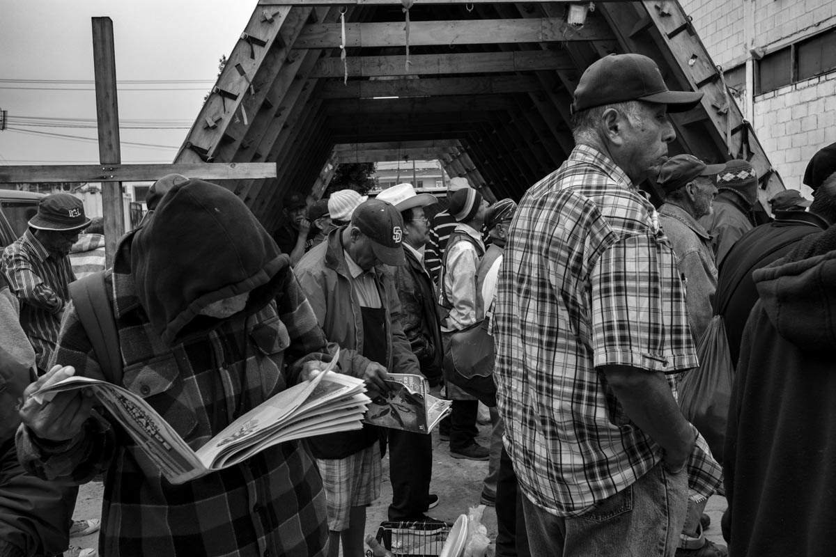 "TIJUANA, BAJA CALIFORNIA, MEXICO - MARCH, 2017: A group of illegal immigrants who try to get to the US or who have been deported stand in line for breakfast in the Salesian dining room ""Padre Chava"""