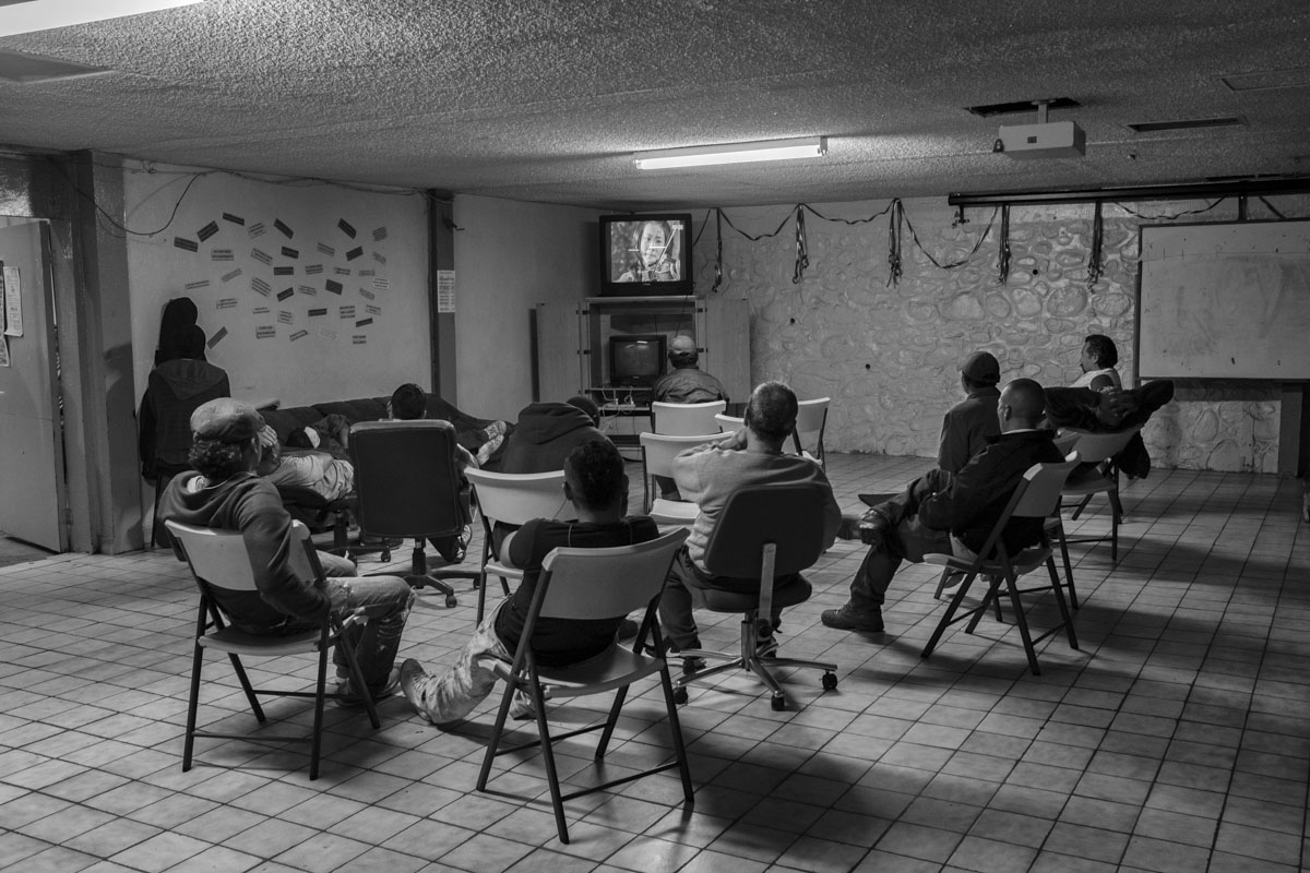TIJUANA, BAJA CALIFORNIA, MEXICO - MARCH, 2017: A group of illegal immigrants and deportees watch TV at the migrant's home in TIjuana, Mexico.