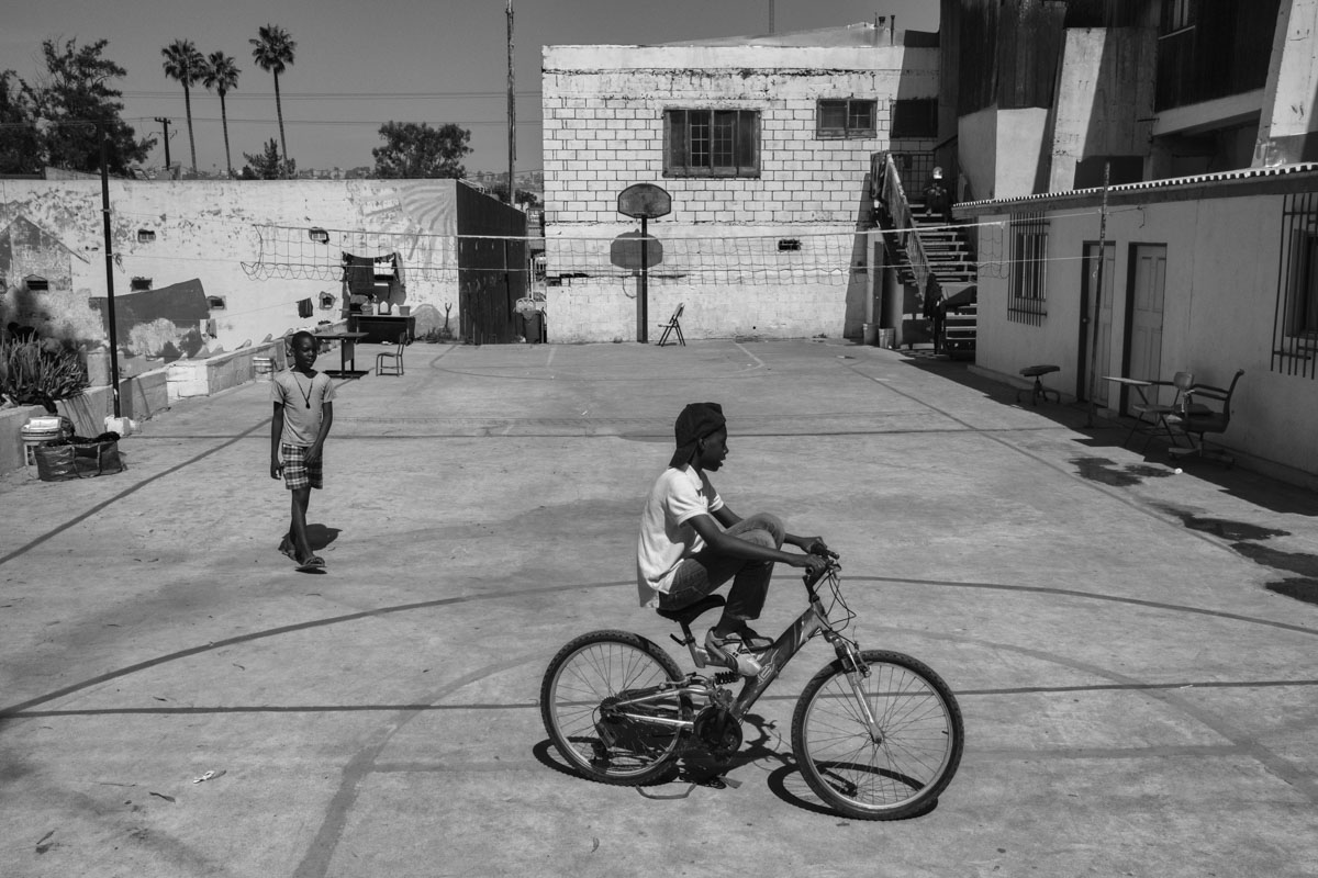 "TIJUANA, BAJA CALIFORNIA, MEXICO - MARCH, 2017: A group of Haitian kids refugee playin the improvised abergue of the ""Jueves 2021"". During the last year an avalanche of Haitian emigrants arrived in Tijuana trying to cross into the US. Most of the refugees were rejected by the US and currently live on charity in TIjuana in a total legal limbo."