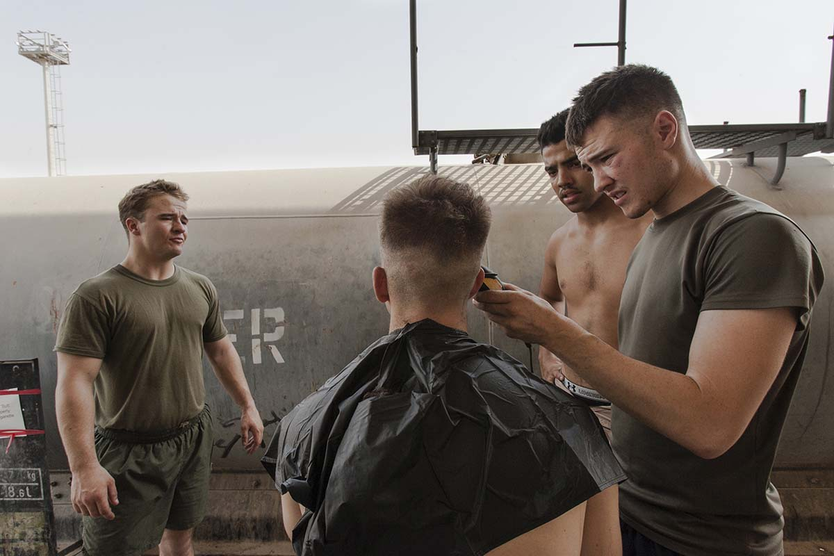 FALLUJAH, IRAQ - JULY 2006: US marines from Bravo Company takes turns having their hair cut during their free time. Fallujah continues to be a symbol for the Iraqi resistance, and is the most insurgent-hit city of Iraq, full of destruction, dust, and dead. Since the major US troop operations in 2005, the daily lives of civilians and marines inside the city have become a fight to stay alive.