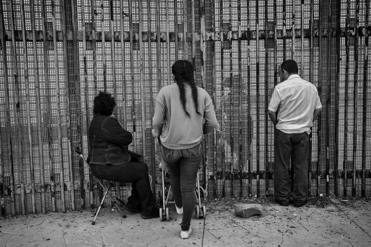 TIJUANA, BAJA CALIFORNIA, MEXICO - MARCH, 2017: A family separated because of deportation is scheduled to speak at the Tijuana Friendship Park. Each weekend, hundreds of families separated by the wall are cited to see their loved ones in the border wall that delimits the border between Mexico and the US.