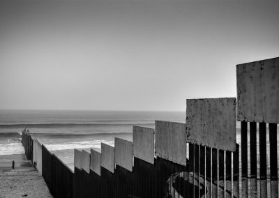 TIJUANA, BAJA CALIFORNIA, MEXICO - MARCH, 2017: A couple of tourists takes photos while she simulates climbing the border wall between Mexico and the US. The wall has become a tourist attraction since the arrival in the White House of Donald Trump. The town of Playas de TIjuana is a place of contradictions where every Sunday thousands of tourists gather on one side and on the other families dismembered because of the wall and deportations.