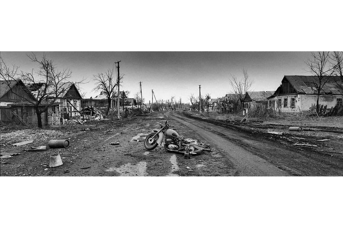 DONESTK, UKRAINE - FEBRUARY 2015: The remains of a motorcycle rest on the main street of what once was the community of Nikishino.Nikisino has been one of the major front lines in the war in the East of Ukraine. After the fall of the strategic town of Debaltseve in separatist hands, Ukrainian troops also left this strategic line of the front leaving the community fully mined and converted into ashes. The remains of the Nikishino community attest to the drastic consequences of the war on the civilian population in the East of Ukraine.