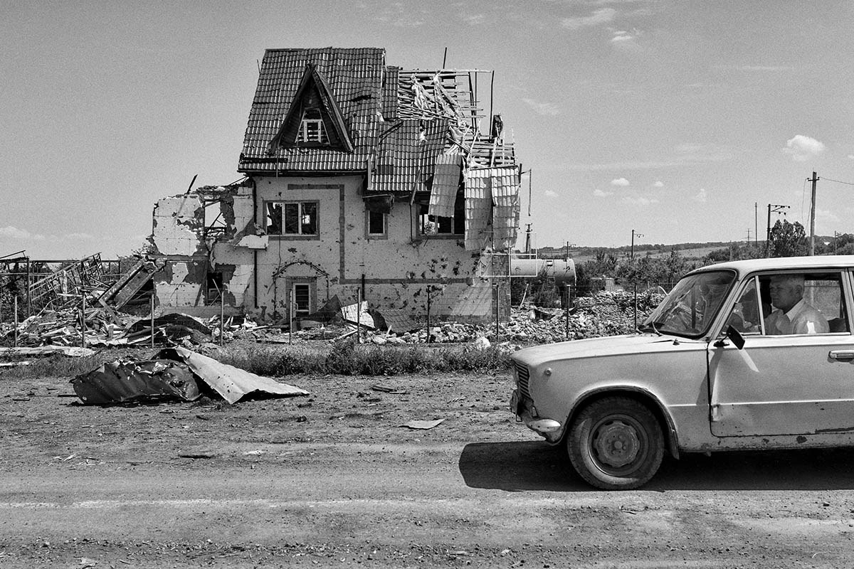 SLAVYANSK, UKRAINE - JULY 11: A group of locals drives past a destroyed house on July 11, 2014 in the village of Semyonovka, near the eastern Ukrainian city of Slavyansk. Pro-Russian separatists in the Donetsk and Luhansk regions declared independence from Kiev and proclaimed their own people's republics after Russia annexed the Crimean peninsula from Ukraine in March. More than 2,000 civilians and combatants have been killed since mid-April, when Ukraine's government sent troops to put down the rebel uprising. Ukraine accuses Russia of arming the rebels and sending Russian soldiers into eastern Ukraine - a claim denied by the Kremlin.