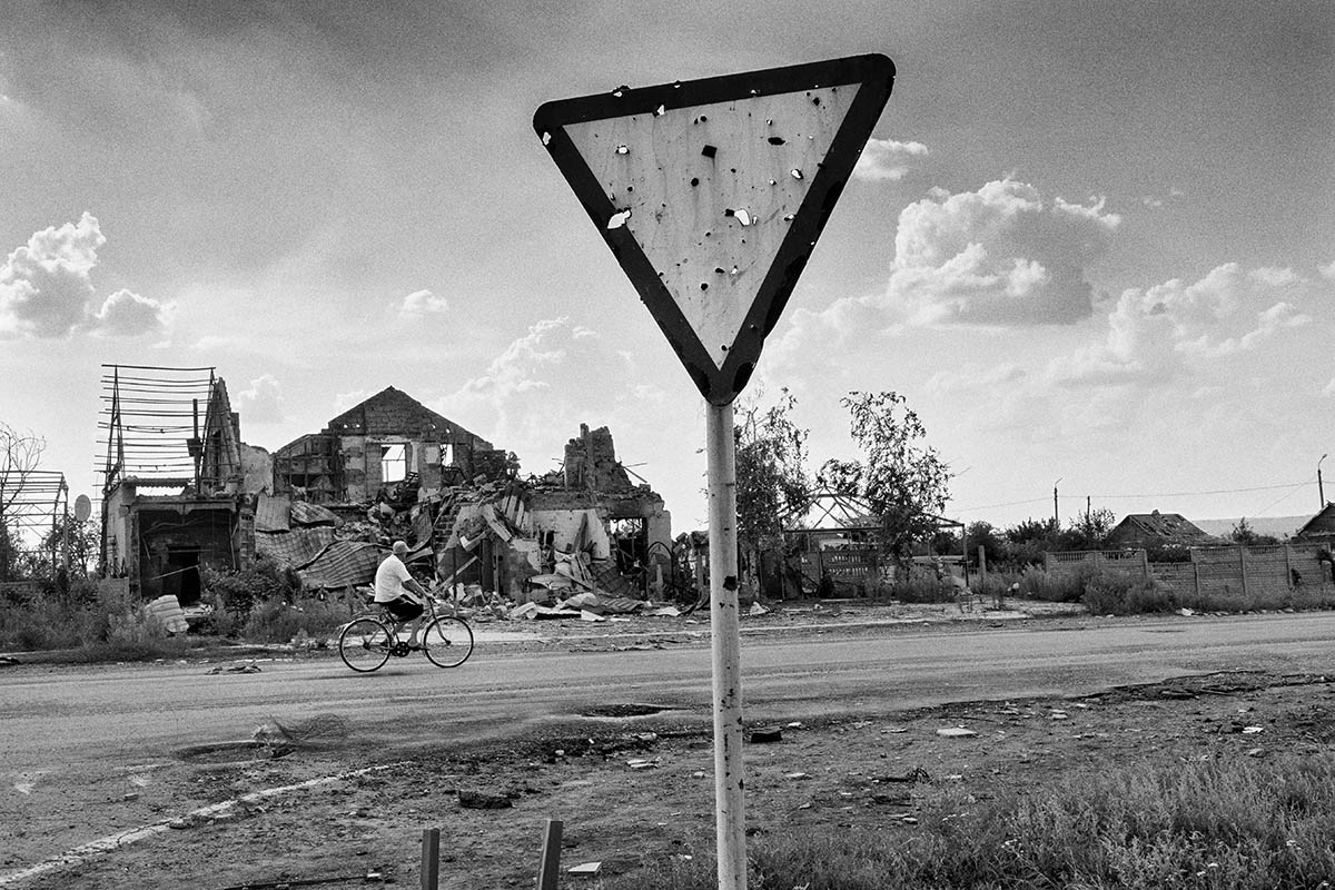 SLAVYANSK, UKRAINE - AUGUST 10: A local drives past a destroyed house on August 10, 2014 in the village of Semyonovka, near the eastern Ukrainian city of Slavyansk. Pro-Russian separatists in the Donetsk and Luhansk regions declared independence from Kiev and proclaimed their own people's republics after Russia annexed the Crimean peninsula from Ukraine in March. More than 2,000 civilians and combatants have been killed since mid-April, when Ukraine's government sent troops to put down the rebel uprising. Ukraine accuses Russia of arming the rebels and sending Russian soldiers into eastern Ukraine - a claim denied by the Kremlin.