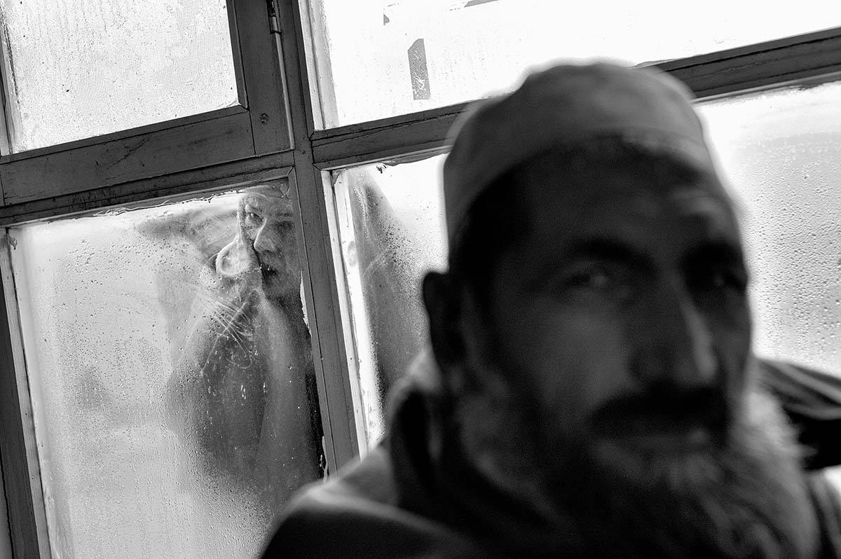 KABUL, AFGHANISTAN - FEBRUARY 2009: With temperatures below freezing, a woman peers through the window into the waiting room of Institute for Malaria and Leishmaniasis, which receives 50 new patients per day, and 200 returning patients. These illnesses are spread through mosquitos, who are able to reproduce readily in the crumbling houses of Kabul. Their bites can cause skin infections and internal ulcers which inflame the spleen and liver, and can end up being fatal. There are so many cases that the medicine used as an effective treatment if taken for a month and half, at the cost of around USD $150, is running out. Afghanistan has become the key war zone for the new US administration. After years of focus on Iraq, the US government has realized how critical an issue Afghanistan really is. It is a country all too used to broken promises, used to death and used to fighting for its survival. Afghans have increasingly lost hope, and have lost faith in the promises made by the Western World. They now seem focussed on daily survival despite the hardships and social issues that they face on a constant basis.