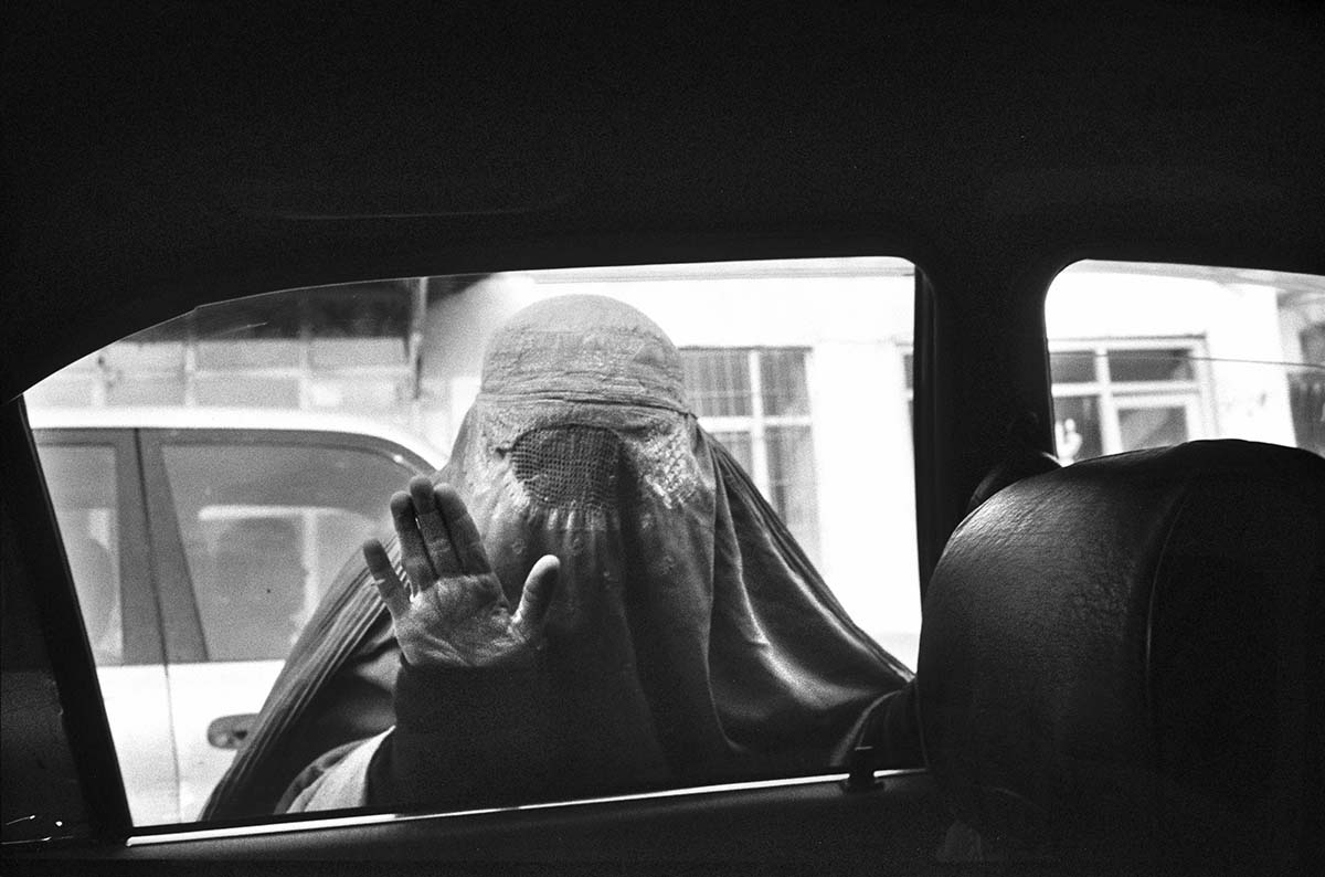 KABUL, AFGHANISTAN - FEBRUARY 2009: A woman wearing a burqa begs for money through a car window in Kabul. Wrapped in their burqas, this society which descriminates against women gives widows little option to beg, in the absence of their deceased husbands. Afghanistan has become the key war zone for the new US administration. After years of focus on Iraq, the US government has realized how critical an issue Afghanistan really is. It is a country all too used to broken promises, used to death and used to fighting for its survival. Afghans have increasingly lost hope, and have lost faith in the promises made by the Western World. They now seem focussed on daily survival despite the hardships and social issues that they face on a constant basis.